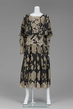 Geoffrey Beene Woman's suit with over-the-head blouse of black chiffon patterned with beige flowers, front and sleeves appliqued with black and beige lace, neck and cuffs gathered with ruffle collar and cuff; full shirt of chiffon shirred at waist and trimmed at hem with lace; unstructured cropped jacket with 3/4 sleeves of chiffon, quilted with black wool backing to give shape, trimmed with gold lame piping. Spring 1982