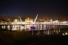 """LONDONDERRY, NORTHERN IRELAND - JANUARY 30:  Floodlights illuminate the Peace Bridge on the River Foyle on January 30, 2013 in Londonderry, Northern Ireland. A year of events have started as Derry celebrates being the City of Culture for 2013. Known locally as """"Stroke City"""" - Derry, stroke, Londonderry. Before the late 1600's it was Derry & after the siege given the prefix London. Long memories, & old battles!"""