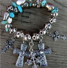 Five Crosses with Turquoise Chips Stretch Bracelet    Two rows of Burnished silver beads mixed with turquoise chips make up the back of this bracelet    Five Crosses, some with rhinestones hang from a row of burnished silver beads.     $14.99