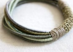 ragtales bracelet - Silk embroidery threads in subtle shades of dusty green, sage and taupe are tightly wound around 7 leather cords, to create bracelet. The silk bound cords are secured with a band of hand crocheted silk thread.