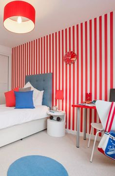 Cool teenager boy's bedroom, with red striped wallpaper and desk and complementary white and blue decor in a modern Edinburgh home.