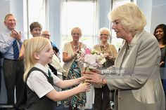 Camilla, Duchess of Cornwall receives flowers from Sophie Booker, aged 10,during a visit to Ballyhackamore Credit Union on May 21, 2015 in Belfast, Northern Ireland. Prince Charles, Prince of Wales and Camilla, Duchess of Cornwall will attend a series of engagements in Northern Ireland following their two day visit in the Republic of Ireland.