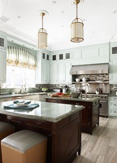 Dream kitchen with two kitchen islands!  Also love the pale gray/blue/green cabinets with the contrasting dark wood islands!