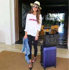 Arielle Noa Charnas wears a graphic long-sleeve t-shirt, black leggings, Valentino flats, a fedora, and a fedora