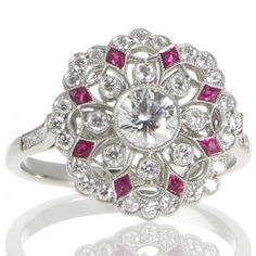 A platinum cluster ring featuring a central 0.38ct brilliant cut diamond bezel set to the centre surrounded by individually bezel set diamonds highlighted with fancy cut rubies. www.rutherford.com.au