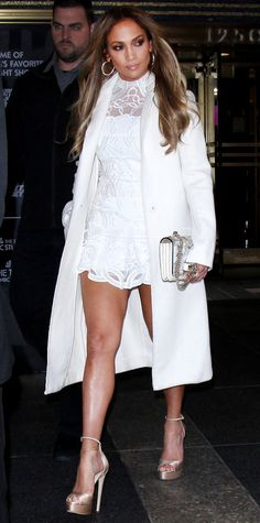 Jennifer Lopez demoed how to wear an all white ensemble while out in New York City. She wore a lace mini dress by Jonathan Simkhai under a crisp coat styled with a white chain strap bag and sky high satin sandals.