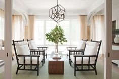 Lillian August - living rooms - spindle chairs, black spindle chairs, abacus chairs, black abacus chairs, chairs facing each other, wood waterfall coffee table, green diamond rug, diamond print rug, faceted pendant, glass and iron chandelier,
