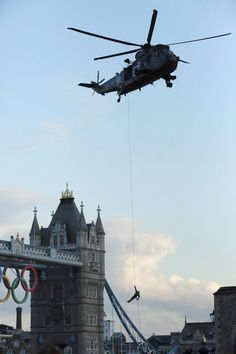 Olympic torch arrives in London - A Royal Marine abseils from a helicopter with the Olympic flame in front of the Tower of London, central London, July 20, 2012. REUTERS/Olivia Harris (BRITAIN - Tags: SPORT OLYMPICS).
