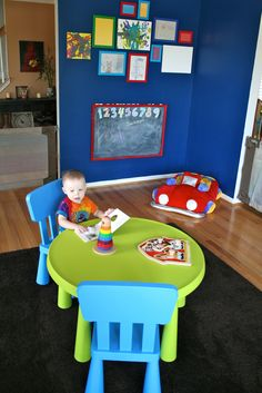 like the table and kids art work framed on wall