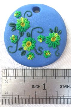 Polymer clay pendant, handmade with applique technique, one of a kind. Light sparky blue with flowers in yellow to vibrant green gradient, dark green leaves and swirls. By Lis Shteindel.