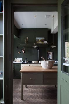 Dark green kitchen island with wood countertop by Plain English.