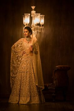 This ornate beige tulle paneled lehenga has been done in floral zardosi in the unusual shade of rose gold, highlighted by tonal resham threads, complete with a nakshi peeta checkered border. This is teamed with a matching cholee and a dupatta with antique jaal all over. The unique charm of the champagne color makes it perfect for pheras and reception.