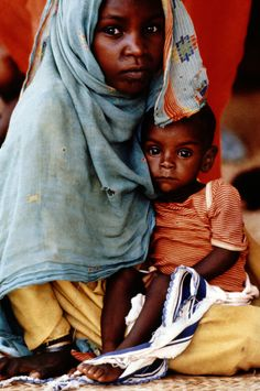 Young girl with baby brother at feeding clinic in Khartoum, Sudan, 1987.
