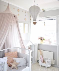 Girl's pastel dream room, with bed canopy and star garland, hot air balloon and Maileg bunny in a little doll crib. #bunnyinthewindow