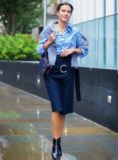 Alexa Chung wears a button-down shirt, blue wrap skirt, bunny-shaped clutch, and zip-up ankle boots