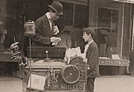 Joseph Severio, peanut vender, age 11 [seen with photographer Hine]. Been pushing a cart 2 years. Out after midnight on May 21, 1910. Ordinarily works 6 hours per day. Works of his own volition. All earnings go to his father. Wilmington, Delaware.