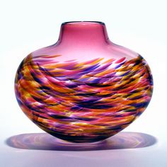 Low Flat Vortex Vase: Cranberry by Michael Trimpol, Monique LaJeunesse. A swirl of *polychrome* *blown glass* culminating in a cranberry neck. The coloring will vary based on lighting. Signed on bottom.