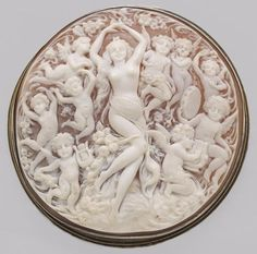 A shell cameo pendant-brooch, circa 1880. in the image of Venus and her putti surrounding; mounted in silver; dimensions: 3 5/16 x 3 1/4in.