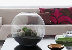 O globo transparente chama atenção na mesa de centro, com um microjardim de cactos e suculentas. Autora da montagem, a designer de jardim Caroline Saccab Haddad Zakka, da Secret Garden, usou uma base de areia preta para encaixar os vasinhos plásticos