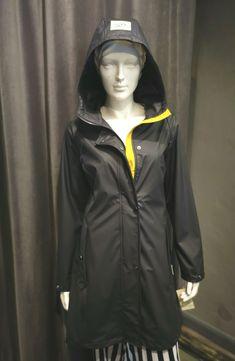 Dieser matt schwarze Regenmantel von Frandsen ist ganz leicht und perfekt für Frühjahr, Sommer und Herbst geeignet. Das ganz besondere Highlight ist ein Schmuckelement mit weiß und schwarzen Punkten auf der unteren Rückseite sowie die Schulterpasse auf dem Rücken. Der Regenmantel innen dünn unterfüttert. Die Kapuze ist nicht abnehmbar und die Nähte sind verschweißt, damit kein Wasser eindringen kann. Der lange Reißverschluß in Schwarz ist vorn gelb unterlegt. Raincoat, Jackets, Fashion, Black Raincoat, Long Raincoat, Rain Jacket, Spring Summer, Fall Winter, Cowl