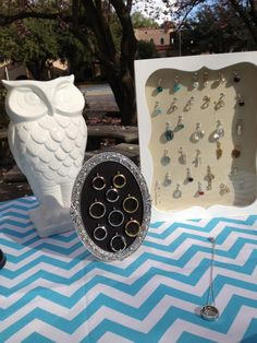 Origami Owl Jewelry Bar display, lockets in a picture frame, dangles in a shadow box, with white owl vase and chevron fabric for table clothe.