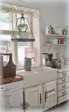 This is an unusually decorated country kitchen. But, the thing that surprises me, is how they fit a farm sink into existing old cabinets. I thought that the cabinetry had to be built around the sink. Good to know.