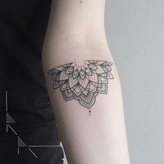 Half mandala tattoo on the left inner forearm.
