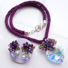 This is my New colour ....! Plum jewelry set handmade using Swarovski elements and Satin cord for necklace. - Pendant handmade with wire technique using Swarovski elements 2.8 x 2.8 cm Heart shape pendant crystal AB (Xillon),4mm Bicone shape in Amethyst,Amethyst Opal,Green. @Pendant size w 3.0 cm x L 4.5 cm. - Necklace handmade Kumihimo technique using Plum colour satin cord. @ Necklace size 18 - Earrings (Stud on) handmade using Swarovski elements 1.4 cm heart pendant, 4 mm bicone shape…