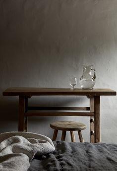 Rustic-luxe furnishings at La Granja Ibiza, neutral tones, linen, grey wall, antiques, stool, beige