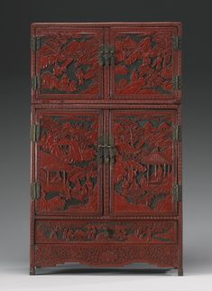 A CINNABAR LACQUER SMALL CABINET  QING DYNASTY, 19TH CENTURY of rectangular form, with a smaller compartment above a larger one, opening to reveal a pair of small drawers, the doors depicting scenes of scholars engaged in 'The Four Accomplishments', all in lakeside settings surrounded by trees and rocky mountains in the background, each door framed with key-fret borders and with gilt-metal lockplates and hinges cast with scrollwork