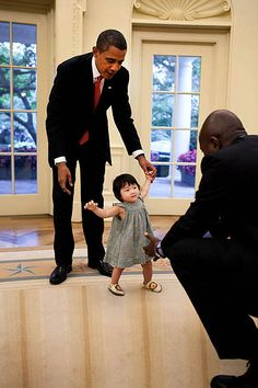 President Barack Obama helps his niece, Savita, as she begins to walk towards the President's personal aide Reggie Love in the Oval Office, Sept. 17, 2009.   (Official White House Photo by Pete Souza)  This official White House photograph is being made available only for publication by news organizations and/or for personal use printing by the subject(s) of the photograph. The photograph may not be manipulated in any way and may not be used in commercial or political materials…