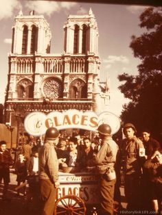American soldiers make purchases of icees at a cart in front of Notre Dame Cathedral. September 1944