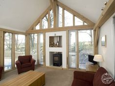 Living Room Interior with Exposed Timber Frame and Glazed Gable End by Carpenter Oak