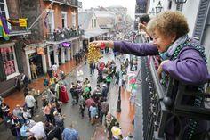 A Mardi Gras reveler dangles a pair of beads off of a balcony on Bourbon Street
