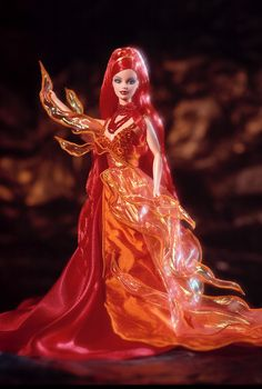DANCING FIRE Barbie (2000) looks radiant in a striking gown inspired by the beauty and intensity of fire. Shell light up a room in her fantasy costume depicting the element of fire. Flame-shaped pieces of iridescent orange taffeta are wired to stand out against the striking gown of red and orange charmeuse. Accessories include a red beaded necklace with a single red faceted drop and matching red bead earrings.