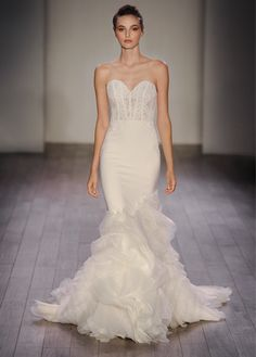 Ivory crepe trumpet bridal gown with organza textured skirt, strapless sweetheart neckline, shear corseted Chantilly lace bodice, natural waist, crepe skirt finished with layered ruffled organza, chapel train. Available in Ivory. Style 3610 by LAZARO