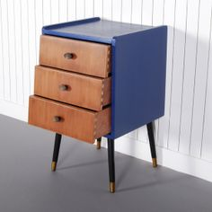 Lowe - £150.00 - The striking blue finish of this 1950s bedside table frames the three angled drawers that sit within and complements the retro gold and black legs. This classic mid-century piece would also serve well as an eye-catching side table adorned with a reading lamp.