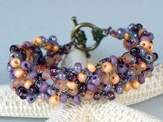 This wire crochet cuff bracelet was made by crocheting, 30 lavender pearl, 30 peach matted, 30 purple silver lined, 30 lavender matted, and 30 orange colored glass seed beads to colored artist wire, forming 5 separate strands of beads. MEMBER - Crochet Hooked