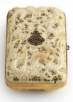 A RUSSIAN JEWELED GOLD-MOUNTED AND IVORY CIGARETTE CASE STRUCK WITH THE STANDARD RUSSIAN MARK FOR 14 CARAT GOLD.  Rectangular box with rounded corners, the cover and base overlaid with ivory cagework intricately pierced and chased with scrolls and sea-serpents, the cover set with the raised gold cypher for Nicolas II (1868-1918), Tsar of Russia 1894-1917, polished gold sides with sapphire cabochon push-piece.