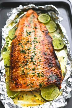 Baked honey cilantro lime salmon in foil is cooked to tender flaky perfection in just 30 minutes with a flavorful garlic and honey lime glaze. Baked Honey Cilantro Lime Salmon in Foil Baked Salmon Recipes, Fish Recipes, Seafood Recipes, New Recipes, Chicken Recipes, Cooking Recipes, Cooking Pasta, Cooking Steak, Cooking Bacon