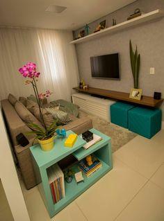 decoracion de pisos pequeños, salon con sofa en marron, estanteria en azul claro con orquidea rosa