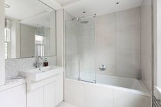 Beautiful and simple modern white bathroom with combined bath and shower. By Granit Chartered Architects