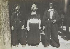 Vrouw en twee mannen in Volendammer streekdracht. Ze zijn gekleed in zondagse dracht. De opname is gemaakt tijdens het 'Vaderlandsch Historisch Volksfeest' te Arnhem, september 1919 #NoordHolland #Volendam