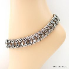 A wide vertebrae weave chainmail anklet for men or women, created from durable stainless steel jump rings. The anklet was hand woven using 3 jump ring sizes in two wire gauges. Medium sized jump rings are perfectly encircled by large rings and the chain is completed with small jump