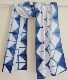 This light weight cotton scarf is hand dyed using a Japanese resist technique to give a unique geometric pattern. The blue is from natural indigo,
