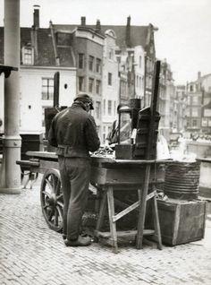 1940. Mussel vendor behind stall with mussels on the Singel near Haarlemmerstraat in Amsterdam. Photo Spaarnestad. #amsterdam #1940 #singel