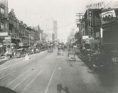 Photo of the 1800 block of Main Street, looking east, Dallas, Texas. The photographer's shadow can be seen at the bottom of the photo. A large hotel can be seen in the distance (in the 1900 block) at Main and Harwood.