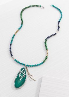 """Santa Marta Necklace  8340   This long statement Necklace brings the exotic colors of Santa Marta to your neckline. Featuring blue and green stones and a stunning Pendant, this Necklace is ready to wear with your bright vacation whites, maxi dresses and slouchy printed pants.  Length: 31.00""""  Material: Agate, Brass, Howlite, Lapis, Quartzite, Sterling Silver"""