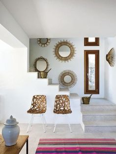 An array of sunburst mirrors and a pair of wrapped rattan chairs combine for an eye-catching composition against this Mallorcan home's crisp white walls.