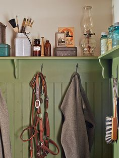 A variety of collectibles—from blue Ball jars to tackle boxes—line the mudroom's ledge, painted Timson Green by Benjamin Moore. #countryliving